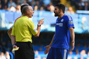 Diego Costa of Chelsea is shown a yellow card by referee Mike Dean during the Barclays Premier League match between Chelsea and Arsenal at Stamford Bridge on September 19, 2015 in London, United Kingdom.