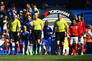 Referee Mike Dean and players walk into the pitch prior to the Barclays Premier League match between Chelsea and Arsenal at Stamford Bridge on September 19, 2015 in London, United Kingdom.