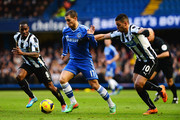 Eden Hazard (C) of Chelsea holds off the challenge of Vurnon Anita (L) and Hatem Ben Arfa (R) of Newcastle United during the Barclays Premier League match between Cheslea and Newcastle United at Stamford Bridge on February 8, 2014 in London, England.