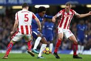 Willian of Chelsea is challenged by Kevin Wimmer and Darren Fletcher of Stoke City during the Premier League match between Chelsea and Stoke City at Stamford Bridge on December 30, 2017 in London, England.