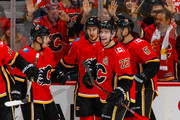 Johnny Gaudreau #13, Mikael Backlund #11, Sean Monahan #23, and Mark Giordano #5 of the Calgary Flames celebrate after scoring the first goal in an NHL game on December 31, 2017 at the Scotiabank Saddledome in Calgary, Alberta, Canada.