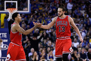 Derrick Rose #1 and Joakim Noah #13 of the Chicago Bulls high-five in the fourth quarter of their game against the Golden State Warriors at ORACLE Arena on January 27, 2015 in Oakland, California. NOTE TO USER: User expressly acknowledges and agrees that, by downloading and or using this photograph, User is consenting to the terms and conditions of the Getty Images License Agreement.
