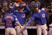 Kyle Schwarber #12 of the Chicago Cubs is congratulated at the plate by Anthony Rizzo #44 and Kris Bryant #17 after hitting a 3 RBI home run in the sixth inning against the Colorado Rockies at Coors Field on April 20, 2018 in Denver, Colorado.