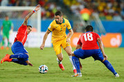 Mathew Leckie of Australia controls the ball as Arturo Vidal of Chile comes in for a tackle during the 2014 FIFA World Cup Brazil Group B match between Chile and Australia at Arena Pantanal on June 13, 2014 in Cuiaba, Brazil.
