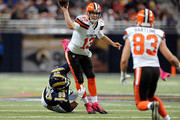 Josh McCown #13 of the Cleveland Browns throws a pass to Brian Hartline #83 as he avoids beinf sacked by Aaron Donald #99 of the St. Louis Rams in the first quarter at the Edward Jones Dome on October 25, 2015 in St. Louis, Missouri.