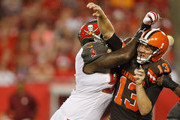 Quarterback Josh McCown #13 of the Cleveland Browns gets pressure from defensive end Henry Melton #90 of the Tampa Bay Buccaneers during the preseason game between the Tampa Bay Buccaneers and the Cleveland at Raymond James Stadium on August 29, 2015 in Tampa, Florida.