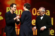 (L-R) Jury President Tom Tykwer hands the Golden Bear for Best Film for 'Touch me not' to Adina Pintilie next to Festival director Dieter Kosslick at the closing ceremony during the 68th Berlinale International Film Festival Berlin at Berlinale Palast on February 24, 2018 in Berlin, Germany.