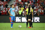 Angel Correa of Atletico Madrid speaks with Petr Cech of Arsenal before taking the penalty kick during the International Champions Cup 2018 match between Atletico Madrid and Arsenal at the National Stadium on July 26, 2018 in Singapore.