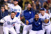 Manny Machado #8, Matt Kemp #27, Alex Verdugo #61, Clayton Kershaw #22 and Chase Utley #26 of the Los Angeles Dodgers, celebrate while waiting for Chris Taylor #3 at home plate, after his solo homerun to win the game 3-2 over the Colorado Rockies during the 10th inning at Dodger Stadium on September 18, 2018 in Los Angeles, California.