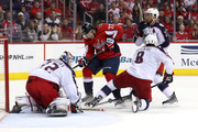 T.J. Oshie #77 of the Washington Capitals and Zach Werenski #8 and goalie Sergei Bobrovsky #72 of the Columbus Blue Jackets go after the puck in overtime during Game Five of the Eastern Conference First Round during the 2018 NHL Stanley Cup Playoffs at Capital One Arena on April 21, 2018 in Washington, DC.
