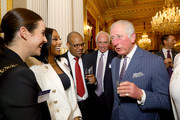 Alexandra Burke (L) and Prince Charles, Prince of Wales (R) attend the Commonwealth Day reception 2020 on March 9, 2020 in London, England.