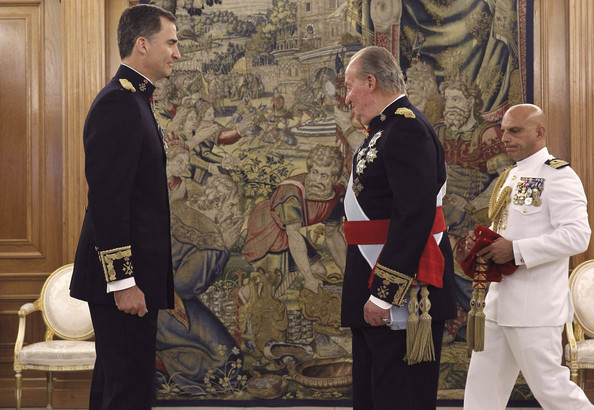 King Juan Carlos prepares to place the sash of the captain general of the armed forces on his son King Felipe VI of Spain in a ceremony held in the Hearing Room Zarzuela Palace, prior to the King's official coronation ceremony on June 19, 2014 in Madrid, Spain. The coronation of King Felipe VI is held in Madrid. His father, the former King Juan Carlos of Spain abdicated on June 2nd after a 39 year reign. The new King is joined by his wife Queen Letizia of Spain.