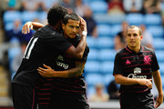 Tim Cahill of Everton is congratulated by team mate Jo and Leon Osman after scoring the opening goal during the pre season friendly match between Coventry City and Everton at the Ricoh Arena on August 2, 2009 in Coventry, England.