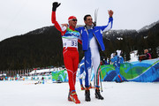 Dario Cologna of Switzerland and Pietro Piller Cottrer of Italy celebrate preliminary gold and silver respectively in the men's cross-country skiing 15 km final on day 4 of the 2010 Winter Olympics at Whistler Olympic Park Cross-Country Stadium on February 15, 2010 in Whistler, Canada.