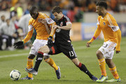 Kofi Sarkodie #8 of the Houston Dynamo controls the ball near the sideline as Chris Pontius #13 of the D.C. United applies pressure as Giles Barnes #23 looks on during second half action at BBVA Compass Stadium on March 2, 2013 in Houston, Texas. Houston won 2-0.