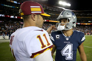 Alex Smith #11 of the Washington Redskins and Dak Prescott #4 of the Dallas Cowboys speak after the Washington Redskins defeat the Dallas Cowboys at FedExField on October 21, 2018 in Landover, Maryland.