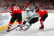 Mattias Janmark #13 of the Dallas Stars plays the puck against Marcus Johansson #90 and Sami Vatanen #45 of the New Jersey Devils on October 16, 2018 at Prudential Center in Newark, New Jersey.