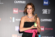 Claudia Gerini poses with the Best Supporting Actress Award at the end of the 62nd David Di Donatello awards ceremony on March 21, 2018 in Rome, Italy.