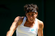 Carla Suarez Navarro of Spain plays a backhand in her Ladies' Singles second round match against Pauline Parmentier of France during Day four of The Championships - Wimbledon 2019 at All England Lawn Tennis and Croquet Club on July 04, 2019 in London, England.