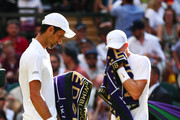 Novak Djokovic of Serbia and Kyle Edmund of Great Britain walk past eachother during a break in play in their Men's Singles third round match on day six of the Wimbledon Lawn Tennis Championships at All England Lawn Tennis and Croquet Club on July 7, 2018 in London, England.