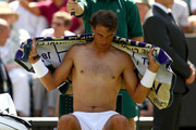 Rafael Nadal of Spain wipes himself with a towel during a break in his Men's Singles first round match against serves against Dudi Sela on day two of the Wimbledon Lawn Tennis Championships at All England Lawn Tennis and Croquet Club on July 3, 2018 in London, England.