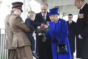 Alfie Lun, 2, is held up by his mother Michelle as he hands a bouquet to Queen Elizabeth II as Prince Philip, Duke of Edinburgh looks on during the unveiling of the new memorial to members of the armed services who served and died in the wars in Iraq and Afghanistan at Victoria Embankment Gardens on March 8, 2017 in London, England.
