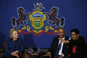 (L-R) Democratic presidential candidate former Secretary of State Hillary Clinton and former attorney general Eric Holder look on as Geneva Reed-Veal speaks during a panel discussion on gun violence at St. Paul's Baptist Church on April 20, 2016 in Philadelphia, Pennsylvania. Hillary Clinton and former attorney general Eric Holder held a panel discussion with parents of victims of gun and police violence.