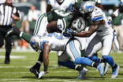 Chris Ivory #33 of the New York Jets is tackled by  Glover Quin #27 and  James Ihedigbo #32 of the Detroit Lions in the first quarter at MetLife Stadium on September 28, 2014 in East Rutherford, New Jersey.