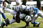 Chris Ivory #33 of the New York Jets is tackled by  DeAndre Levy #54 and  Isa Abdul-Quddus #42 of the Detroit Lions in the first quarter at MetLife Stadium on September 28, 2014 in East Rutherford, New Jersey.