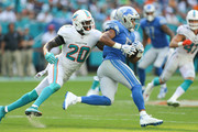 Golden Tate #15 of the Detroit Lions runs with the ball after a reception, chased by Reshad Jones #20 of the Miami Dolphins during the second half at Hard Rock Stadium on October 21, 2018 in Miami, Florida.