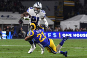 Aqib Talib #21 of the Los Angeles Rams tackles Ezekiel Elliott #21 of the Dallas Cowboys in the second quarter in the NFC Divisional Playoff game at Los Angeles Memorial Coliseum on January 12, 2019 in Los Angeles, California.