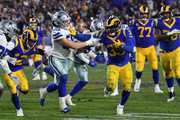 C.J. Anderson #35 of the Los Angeles Rams stiff arms Leighton Vander Esch #55 of the Dallas Cowboys in the second half in the NFC Divisional Playoff game at Los Angeles Memorial Coliseum on January 12, 2019 in Los Angeles, California.