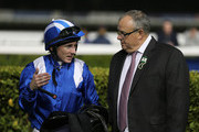Paul Hanagan (L) speaks to Mike de Kock (R) during the first Longines Carnival Meeting at the Meydan Racecourse on January 9, 2014 in Dubai, United Arab Emirates.