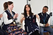 Meghan, Duchess of Sussex smiles after being gifted a jacket from the 'Senior Debate Squad' during a visit to Robert Clack School in Dagenham ahead of International Women's Day (IWD) held on Sunday 8th March, on March 6, 2020 in London, England.