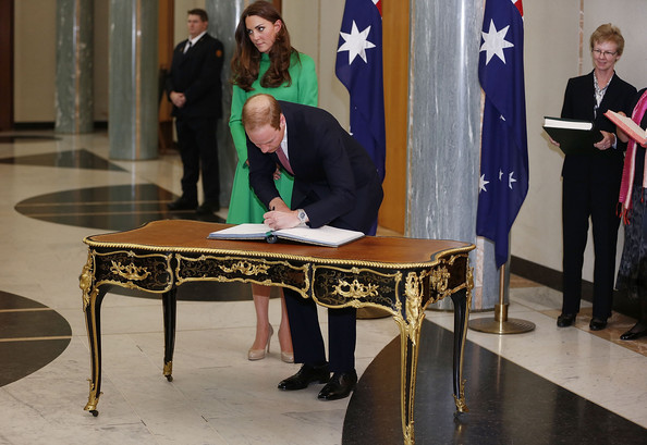 Prince William, Duke of Cambridge and Catherine, the Duchess of Cambridge sign the Prime Minister's and Presiding Officer's Visitors books on the Queen Victoria Writing Table in the Marble Foyer at Parliament House on April 24, 2014 in Canberra, Australia. The Duke and Duchess of Cambridge are on a three-week tour of Australia and New Zealand, the first official trip overseas with their son, Prince George of Cambridge.