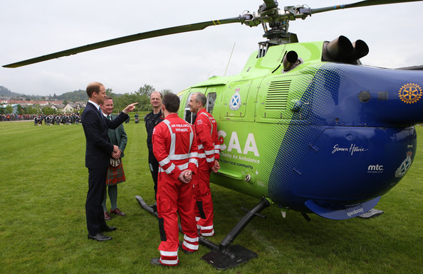 Prince William, Duke of Cambridge (left) talks to Air Ambulance staff during a visit to Strathearn Community Campus on May 29, 2014 in Crieff, Scotland. The Duke and Duchess of Cambridge will spend the day in Scotland where they will tour a distillery and visit a village fete.