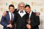 Bart Layton (L) and Dimitri Doganis, winners of the Outstanding Debut By A British Writer, Director or Producer award, pose with presenter Billy Connolly in the press room at the EE British Academy Film Awards at The Royal Opera House on February 10, 2013 in London, England.