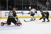 Marc-Andre Fleury #29 and Shea Theodore #27 of the Vegas Golden Knights watch the puck sail away from the net after Fleury blocked a shot by Mark Letestu #55 of the Edmonton Oilers in the first period of their game at T-Mobile Arena on February 15, 2018 in Las Vegas, Nevada. The Golden Knights won 4-1.