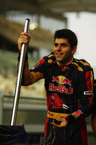 Jaime Alguersuari of Spain acts as the jack-man as he poses with Scuderia Toro Rosso team mates for a team photo in the pitlane during previews to the Abu Dhabi Formula One Grand Prix at the Yas Marina Circuit on October 29, 2009 in Abu Dhabi, United Arab Emirates.