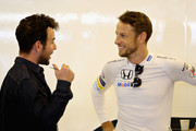 Jenson Button of Great Britain and McLaren Honda talks with cycling superstar Mark Cavendish in the garage before the Abu Dhabi Formula One Grand Prix at Yas Marina Circuit on November 27, 2016 in Abu Dhabi, United Arab Emirates.
