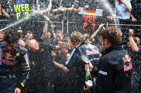 (L-R) Second placed Mark Webber of Australia and Red Bull Racing, Red Bull Racing designer Adrian Newey and race winner Sebastian Vettel of Germany and Red Bull Racing are sprayed with champagne by team mates in the paddock following the British Formula One Grand Prix at Silverstone on June 21, 2009 in Northampton, England.