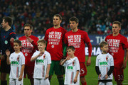 Philipp Lahm, Manuel Neuer, Thomas Mueller and Joshua Kimmich of Bayern Munich wear t-shirts showing support for injured team mate Holger Badstuber as they line up prior the Bundesliga match between FC Augsburg and FC Bayern Muenchen at SGL Arena on February 14, 2016 in Augsburg, Germany.