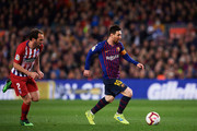 Lionel Messi of FC Barcelona runs with the ball past Diego Godin of Atletico de Madrid during the La Liga match between FC Barcelona and  Club Atletico de Madrid at Camp Nou on April 06, 2019 in Barcelona, Spain.