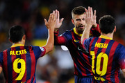 Lionel Messi (R) of FC Barcelona celebrates with his team-mates Gerard Pique (C) and Alexis Sanchez after scoring his team's second goal during the UEFA Champions League Group H match between FC Barcelona and Ajax Amsterdam ag the Camp Nou stadium on September 18, 2013 in Barcelona, Spain.