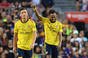 Pierre-Emerick Aubameyang of Arsenal celebrates with his tem mate Mesut Ozil after scoring his team's first goalduring the Joan Gamper trophy friendly match between FC Barcelona and Arsenal at Nou Camp on August 04, 2019 in Barcelona, Spain.