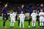 Kids wearing 'Unite against Racism' t-shirt to highlight UEFA's FARE Action Week campaign stand with (L-R) Lionel Messi, Alexis Sanchez and Javier Mascherano of Barcelona during the UEFA Champions League group G match between FC Barcelona and Celtic FC at the Camp Nou stadium on October 23, 2012 in Barcelona, Spain.