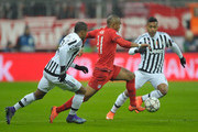 Douglas Costa (C) of Bayern Muenchen challenges Patrice Evra (L) and Alex Sandro of Juventus Turin during the UEFA Champions League Round of 16 second leg match between FC Bayern Muenchen and Juventus Turin at Allianz Arena on March 16, 2016 in Munich, Germany.