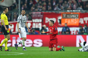 Referee Jonas Eriksson (2st L) prepares for an yellow card after Robert Lewandowski (2nd R) of Bayern Muenchen  and Patrice Evra (1st R) of Juventus collided during the UEFA Champions League round of 16, second Leg match between FC Bayern Muenchen and Juventus at the Allianz Arena on March 16, 2016 in Munich, Germany.