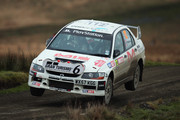 Tony Jardine and co-driver Amy Williams of Great Britain drive their Mitsubishi Lancer Evolution IX over  a jump on the Sweet Lamb stage of the FIA World Rally Championship Great Britain on November 15, 2013 in Llanidloes, Wales.