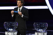 """Uruguay's former forward Diego Forlan shows """"C1"""" during the 2018 FIFA World Cup football tournament final draw at the State Kremlin Palace in Moscow on December 1, 2017..The 2018 FIFA World Cup will be held between June 14 and July 15, 2018 in 11 Russian cities. / AFP PHOTO / Kirill KUDRYAVTSEV"""